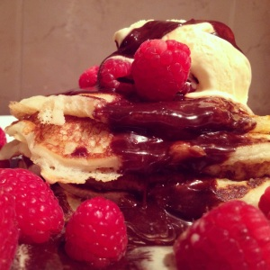 Gluten free American style pancakes with homemade chocolate sauce, raspberries and vanilla ice cream.